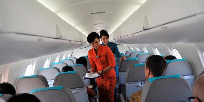 Pramugari Garuda Indonesia melayani penumpang yang mengikuti inaugural flight pesawat terbarunya Bombardier CRJ1000 NextGen dari Makassar tujuan Jakarta. | KOMPAS