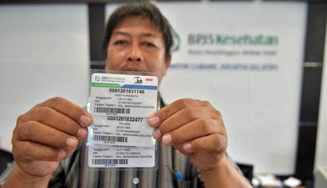 Warga menunjukkan kartu BPJS usai mendaftar sebagai peserta BPJS Kesehatan di Kantor BPJS, Jakarta. FOTO/VIVA