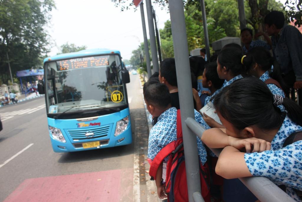 Sejumlah pelajar baru pulang dari sekolah menunggu bus Trans Padang di Halte depan kantor Pemprov Sumatera Barat. FOTO/HUDA PUTRA