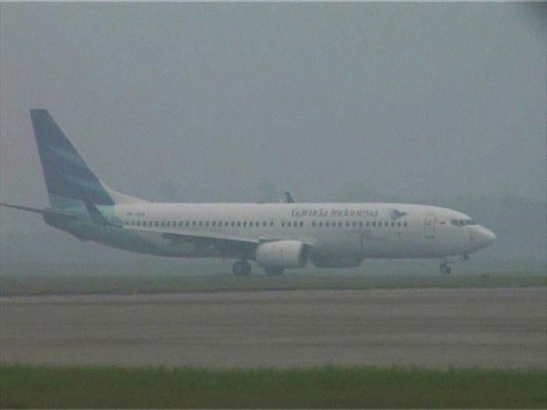 Pesawat Garuda Indonesia tengah mendarat ditengah kepulan asap di Bandara Internasional Minangkabau. FOTO/BUS