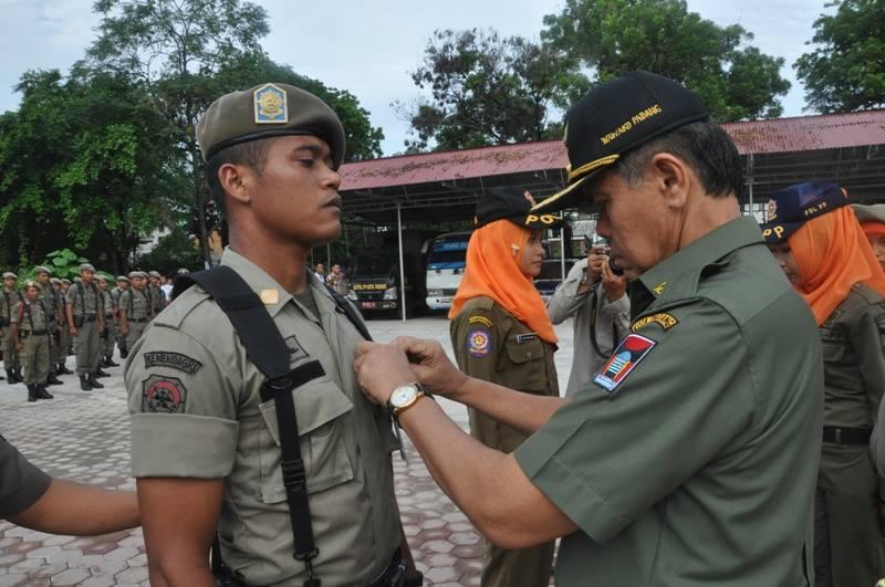 Wakil Walikota Padang, Emzalmi menyematkan pin kepada petugas Satpol PP yang akan bertugas pada empat Kecamatan. Foto : Istimewa