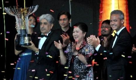 Produser film Sang Kiai Sunil Soraya (kiri) membawa Piala Citra untuk kategori film terbaik, disaksikan Menparekraf Mari Elka Pangestu (tengah) dan Gubernur Jateng Ganjar Pranowo (kanan), pada Malam Penganugerahan Festival Film Indonesia (FFI) 2013 di Mari. Foto : ANTARA